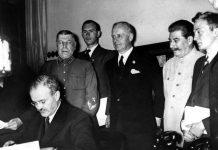 Съветският външен министър Вячеслав Молотов подписва пакта за ненападение между Германия и СССР. На заден план са Йоахим фон Рибентроп и Йосиф Сталин (23 август 1939 г.).